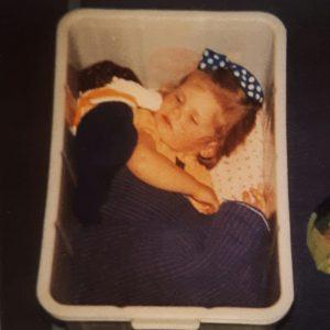 Flicka sover på golvet i en låda.