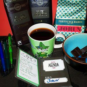 Muminmugg med kaffe, choklad och post-its.